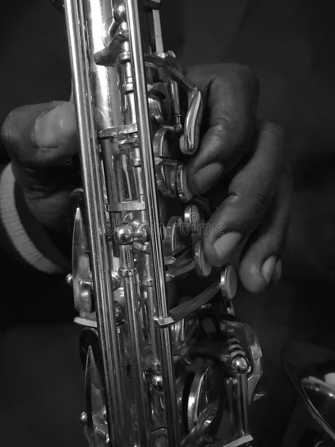 Stäng sig upp av handen på saxofonen i svartvitt royaltyfri bild