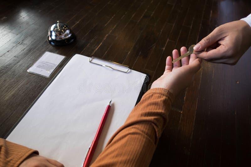 Stäng sig upp av handgäst som tagande hyr rum nyckel- på incheckningskrivbordet av hotellet Hotellbegrepp royaltyfri fotografi