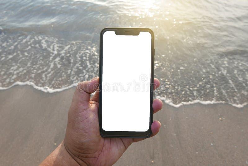 Stäng sig upp av handinnehavtelefonen med den vita skärmen vid stranden Smartphone med modellen på bakgrundsstranden och sand royaltyfri bild