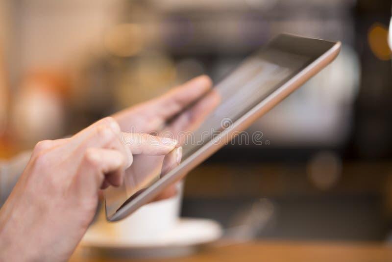 Stäng sig upp av handkvinnan som använder hennes digitala minnestavla I arkivfoto