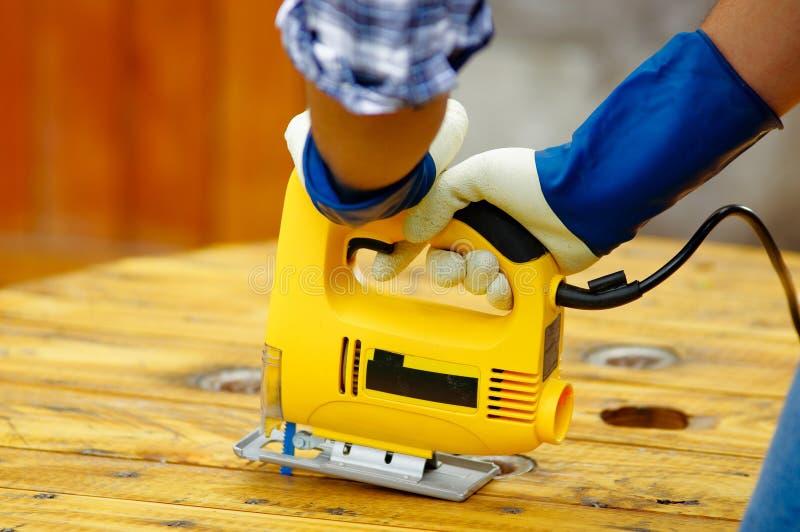 Stäng sig upp av handskar för ett jobb för man som bärande arbetar trä med den elektriska figursågen royaltyfri bild