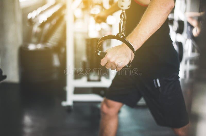 Stäng sig upp av handsportmannen som gör övningsutbildning, den arg färdiga kroppen och muskulöst i idrottshallen fotografering för bildbyråer