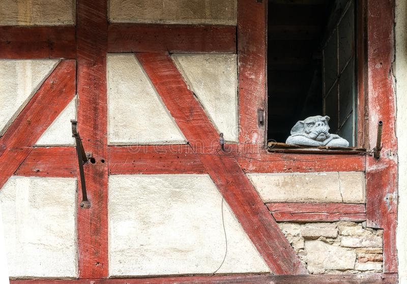 Stäng sig upp av historiskt korsvirkes- bråckbandhus med vita väggar och röda trästrålar och en stenvattenkastarestaty som lutar  royaltyfri fotografi