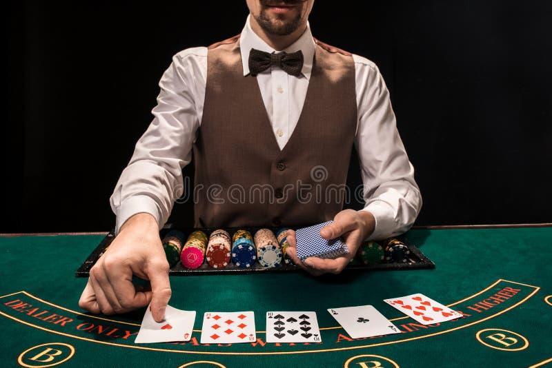 Stäng sig upp av holdemåterförsäljare med att spela kort och chiper på den gröna tabellen fotografering för bildbyråer