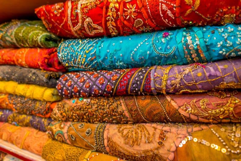 Stäng sig upp av indiska traditionella kvinnasarikläder på marknad Köpandebröllopsari i Jaipur Färgrik härlig sari arkivfoto