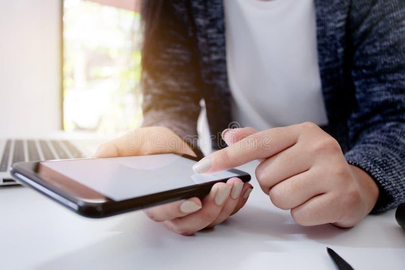 Stäng sig upp av innehavmobiltelefonen för den unga kvinnan, genom att använda den mobila smarta grejen royaltyfria bilder