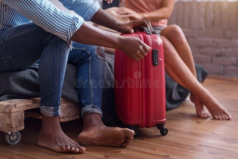 Stäng sig upp av internationella par som förpackar för en resa arkivfoto