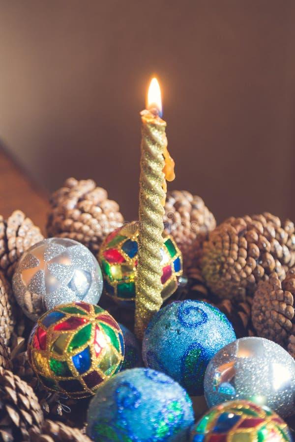 Stäng sig upp av julljuset med färgrik garnering på tabellen royaltyfri bild