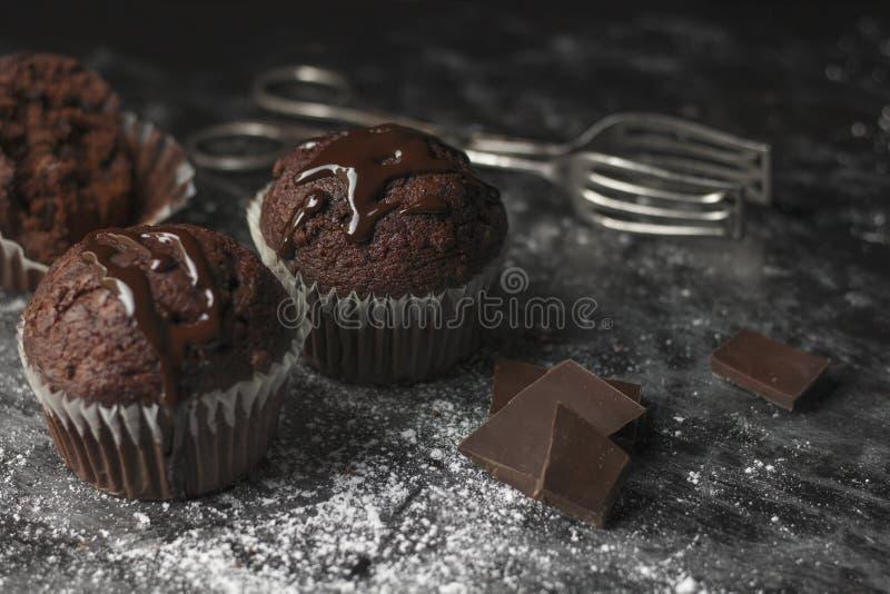 Stäng sig upp av kakaomuffin med chokladisläggning på lantlig tabell c arkivfoton