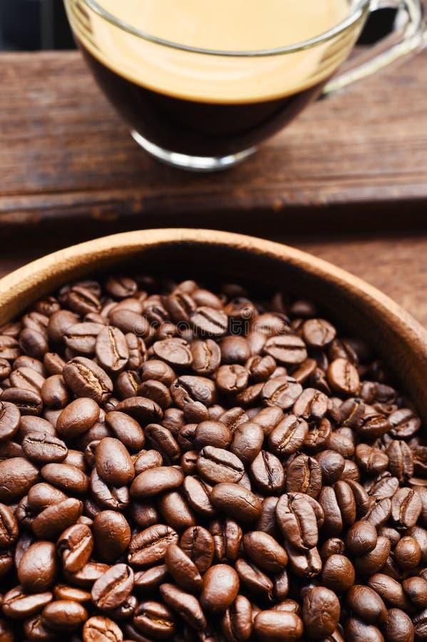 Stäng sig upp av kopp kaffe- och kaffebönan i träbunke royaltyfria bilder