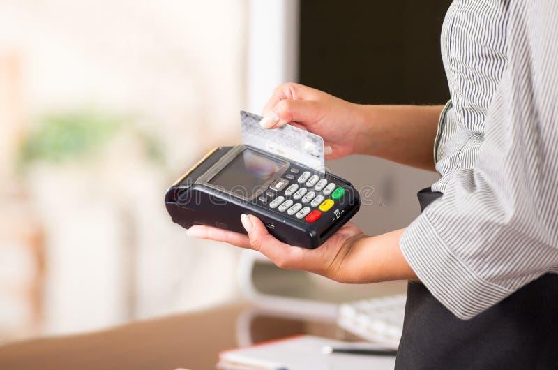Stäng sig upp av kreditkortmaskinen, en kvinnahand som swaping ett grått kort royaltyfria foton