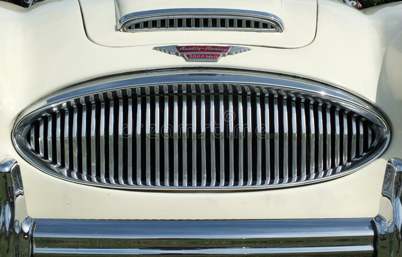 Stäng sig upp av kromgallerstötdämparen, och emblemet av för austin för tappning vita en klassisk sportbil healey 300 på hebden m arkivbild