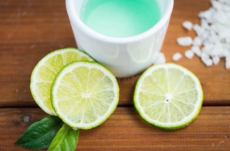 Stäng sig upp av kropplotion i kopp och limefrukter på trä fotografering för bildbyråer