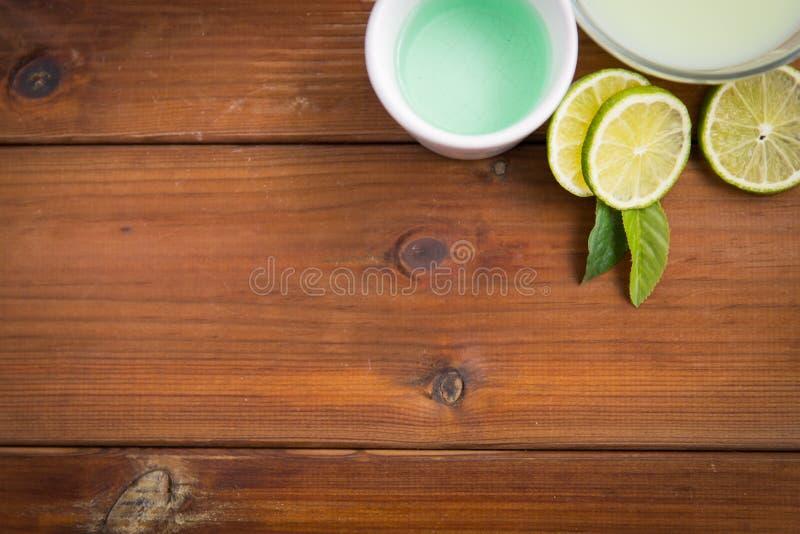 Stäng sig upp av kropplotion, laga mat med grädde och limefrukter på trä arkivfoto