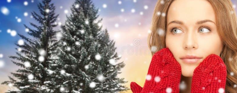 Stäng sig upp av kvinna i tumvanten över julträd arkivbilder