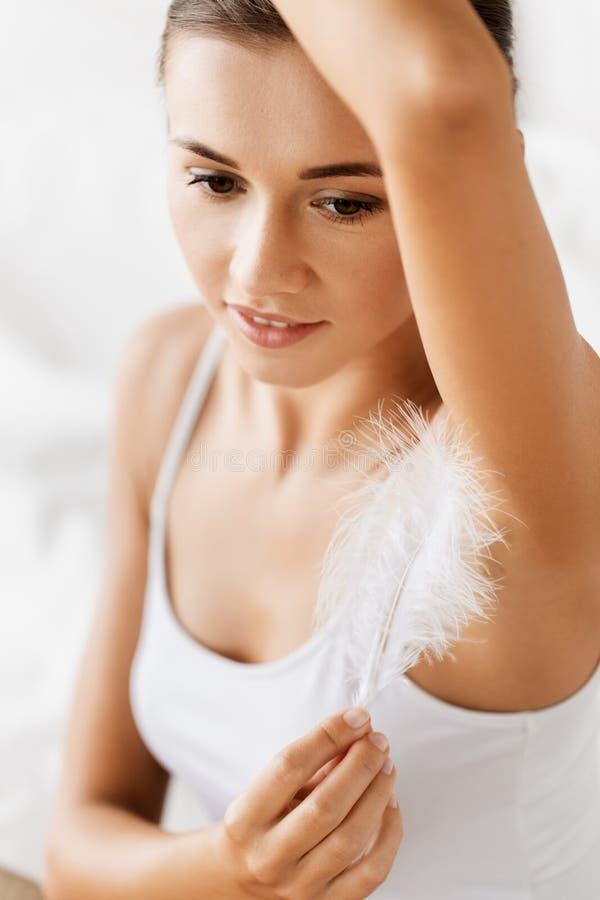 Stäng sig upp av kvinna med fjädern som trycker på hennes armhåla royaltyfri bild