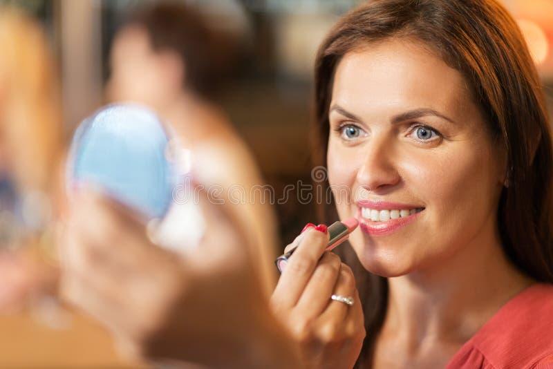 Stäng sig upp av kvinna med läppstift som applicerar makeup arkivbilder