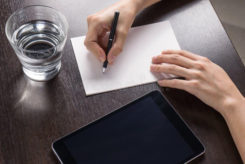 Stäng sig upp av kvinna med minnestavlan och skriv ett papper på den wood tabellen royaltyfria foton