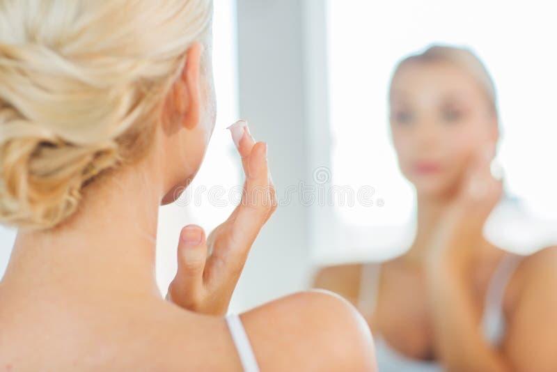 Stäng sig upp av kvinnan som applicerar framsidakräm på badrummet royaltyfria bilder