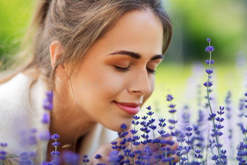 Stäng sig upp av kvinnan som luktar lavendelblommor royaltyfri foto