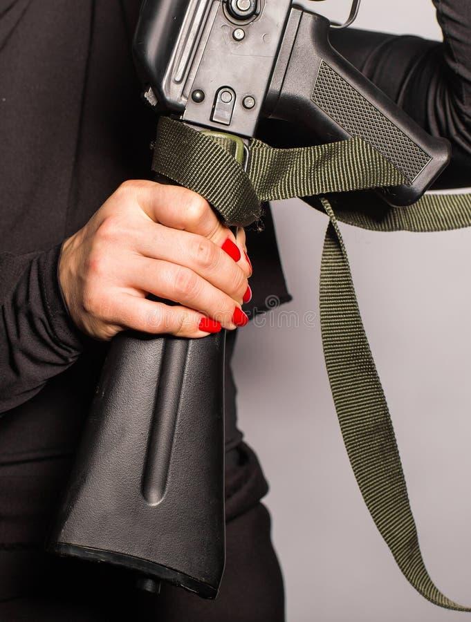 Stäng sig upp av kvinnan som rymmer ett automatiskt anfallgevär royaltyfri bild