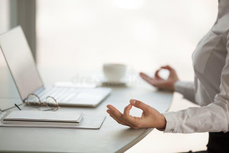Stäng sig upp av kvinnlig anställd som mediterar i lotusblommaposition på arbete arkivbild