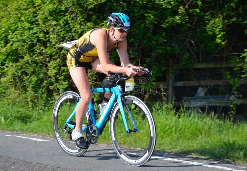 Stäng sig upp av kvinnlig triathlete på vägen som cyklar etappen arkivfoton