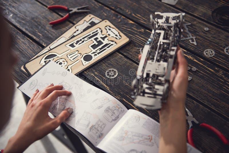 Stäng sig upp av kvinnliga händer med detaljanvisning och metallleksakbilen arkivbilder
