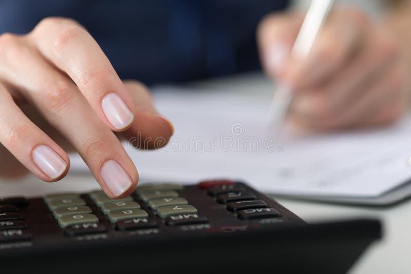 Stäng sig upp av kvinnliga revisor- eller bankirdanandeberäkningar arkivfoto