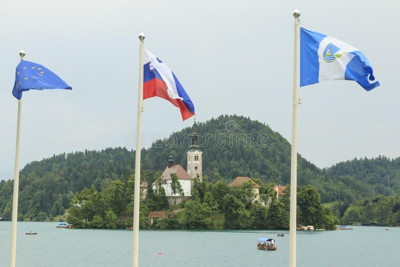 Stäng sig upp av kyrkan i mitten av Bled sjön med flera turister på ett fartyg royaltyfri fotografi
