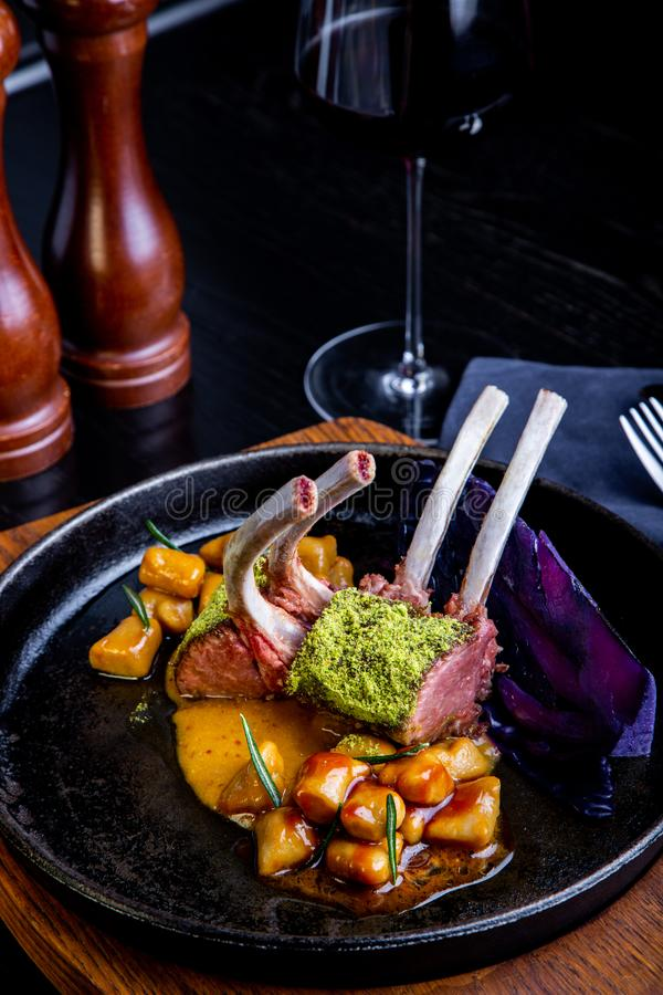 Stäng sig upp av lammkotletter med grönsaker med en sås av karamell, peppar och kryddor i en restauranginställning arkivfoton