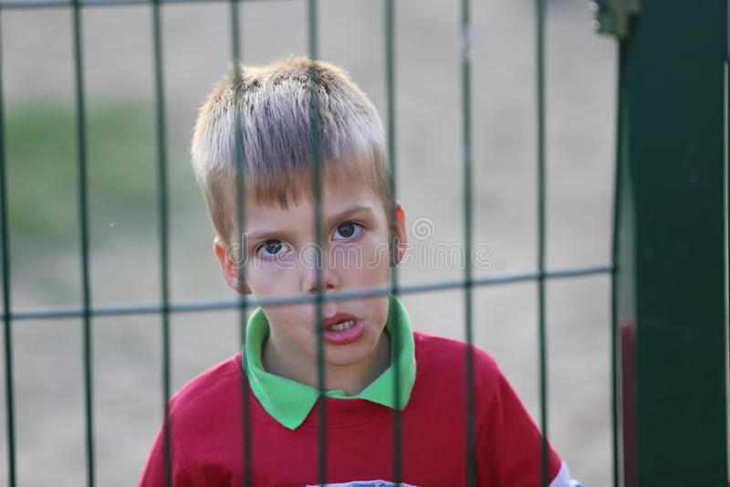 Stäng sig upp av lite pojke bak ett staket fotografering för bildbyråer