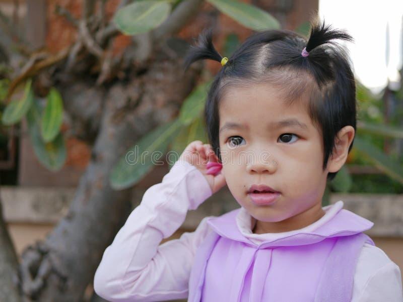 Stäng sig upp av litet asiatiskt, thailändskt, behandla som ett barn flickan som sätter en blomma bak hennes öra arkivbilder