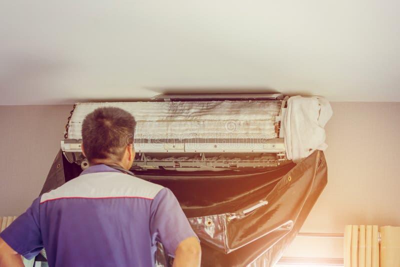Stäng sig upp av luftvillkoret, repairman på golvfixandeluften lurar royaltyfri foto