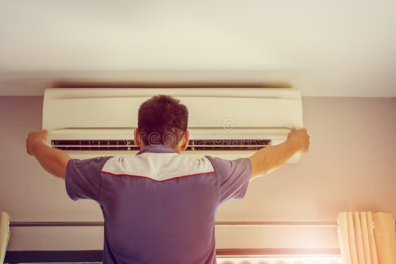 Stäng sig upp av luftvillkoret, repairman på golvfixandeluften lurar royaltyfria foton