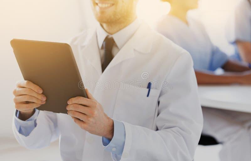 Stäng sig upp av lycklig doktor med minnestavlaPC på kliniken arkivbilder