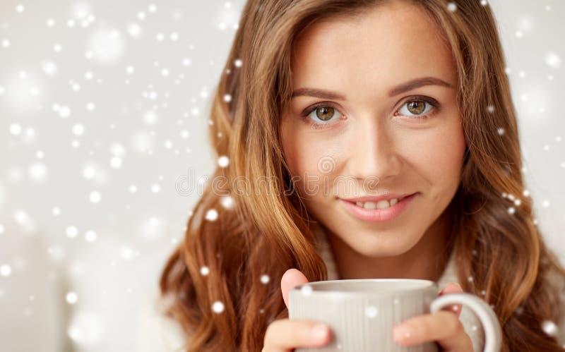 Stäng sig upp av lycklig kvinna med kaffekoppen över snö arkivfoto