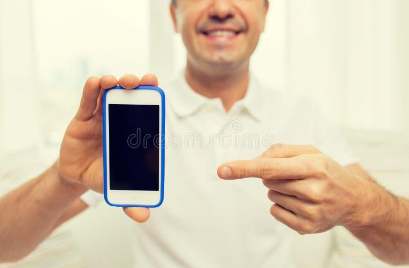 Stäng sig upp av lycklig man med den hemmastadda smartphonen arkivbilder