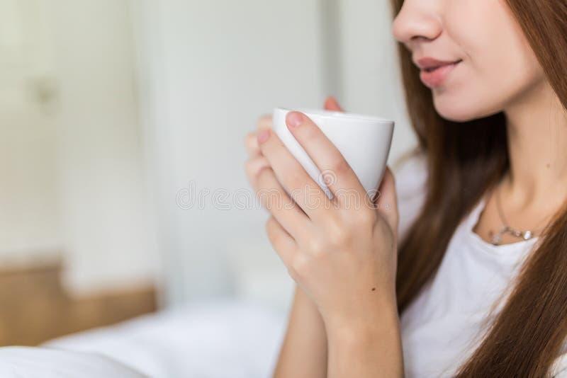Stäng sig upp av lycklig ung kvinna med koppen kaffe eller kakao och katten i säng hemma fotografering för bildbyråer