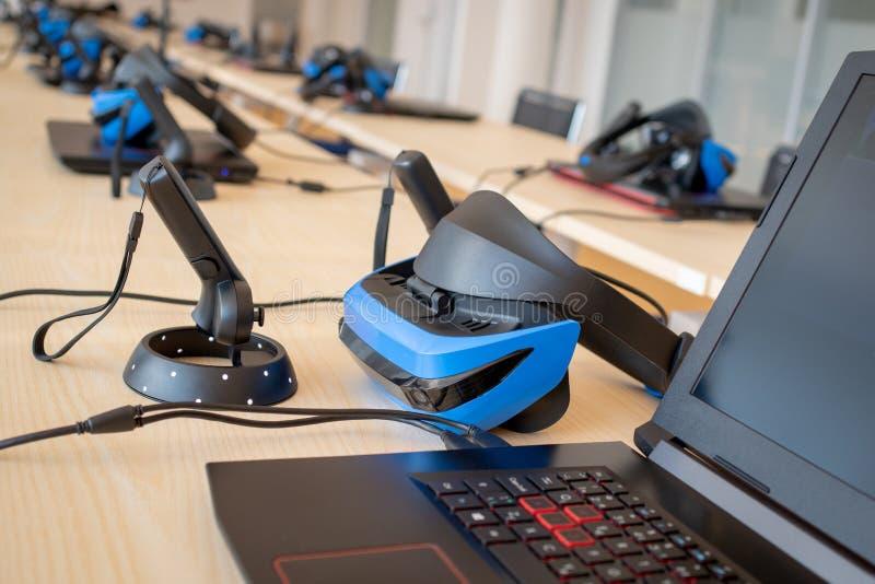 Stäng sig upp av många uppsättningar för virtuell verklighet VR i ett klassrum - hörlurar med mikrofon, kontrollant och dator royaltyfri bild