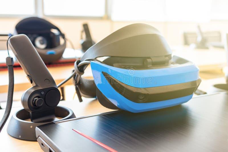 Stäng sig upp av många uppsättningar för virtuell verklighet VR i ett klassrum - hörlurar med mikrofon, kontrollant och dator arkivfoton