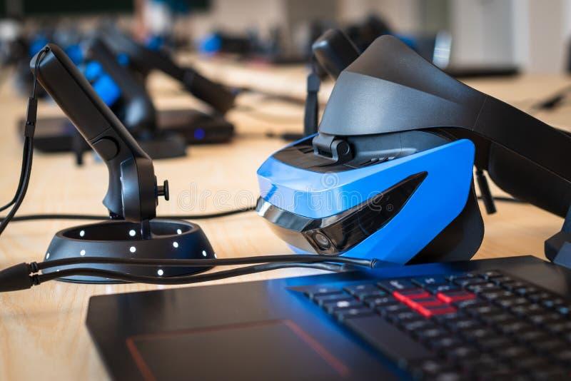 Stäng sig upp av många uppsättningar för virtuell verklighet VR i ett klassrum - hörlurar med mikrofon, kontrollant och dator fotografering för bildbyråer