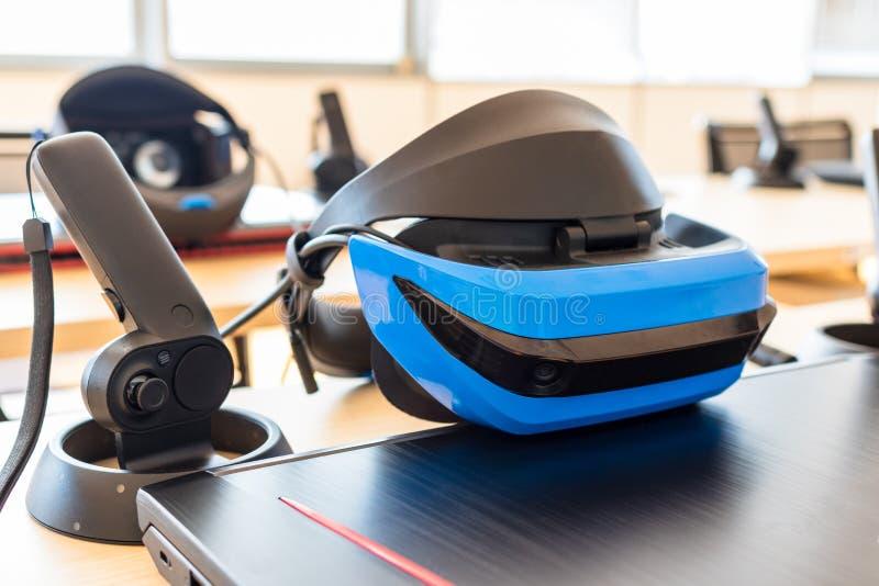 Stäng sig upp av många uppsättningar för virtuell verklighet VR i ett klassrum - hörlurar med mikrofon, kontrollant och dator royaltyfri foto