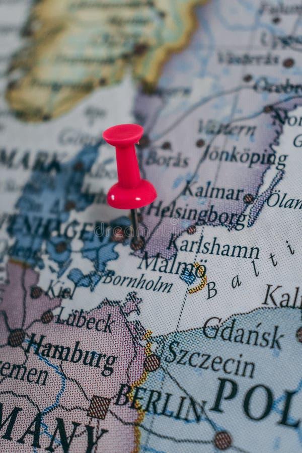 Stäng sig upp av Malmö som stiftet pekade på världskartan med en rosa häftstift royaltyfria foton