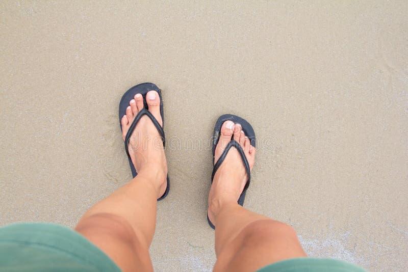 Stäng sig upp av man i svart häftklammermatarefot som står på stranden, royaltyfria foton
