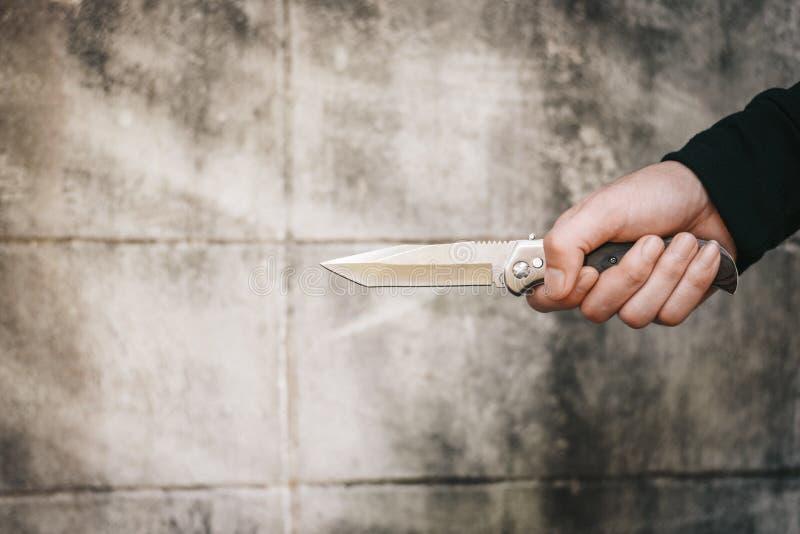 Stäng sig upp av maninnehavkniven Terrorist- och rånarebegrepp pol arkivfoton