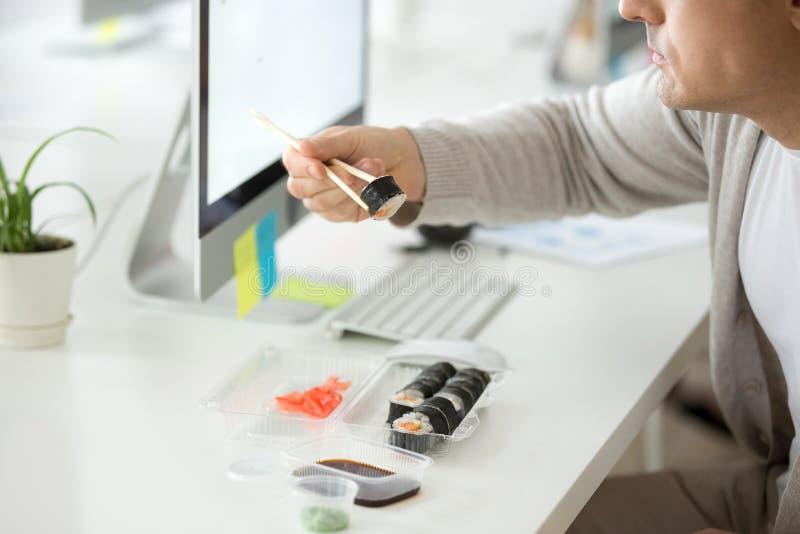 Stäng sig upp av manlig anställd som tycker om sushi på arbetsplatsen royaltyfri foto
