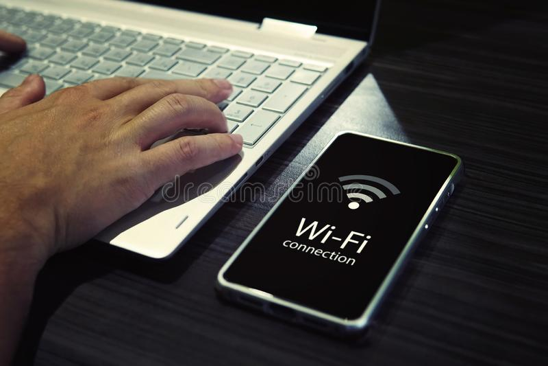 Stäng sig upp av manliga händer som skriver på bärbar datortangentbord och kontrollerar den smartphonewi-fi anslutningen Mobiltel royaltyfria bilder