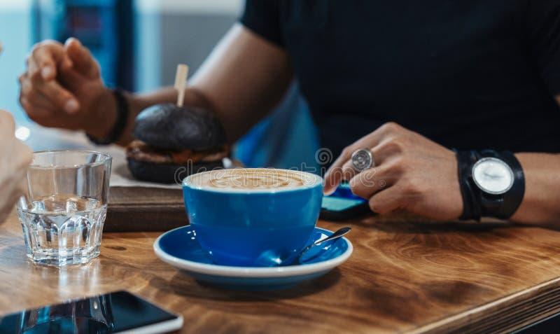 Stäng sig upp av mannen som äter den svarta nya saftiga hamburgaren på kafét och dricker kaffe royaltyfri bild