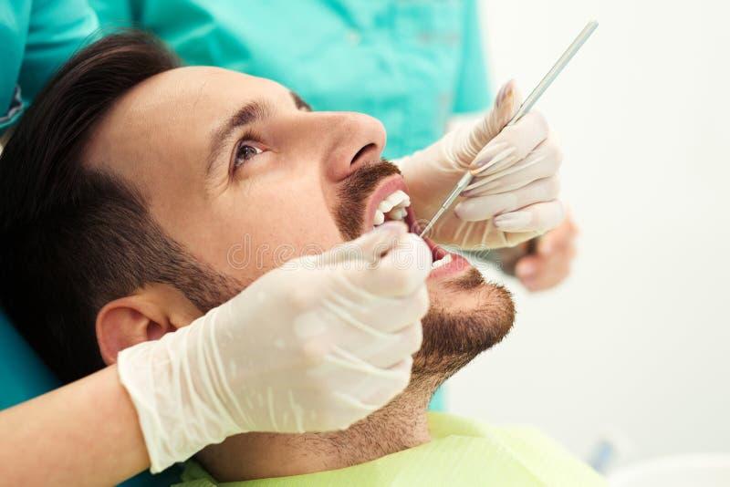 Stäng sig upp av mannen som har hans tänder att undersökas av tandläkaren arkivbilder